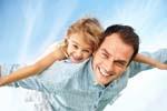 dad giving piggyback ride to daughter